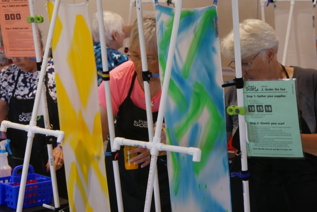 Two retired women painting silk scarves
