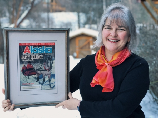 Gina holding framed copy of Dec. 1989 Alaska Magazine cover.