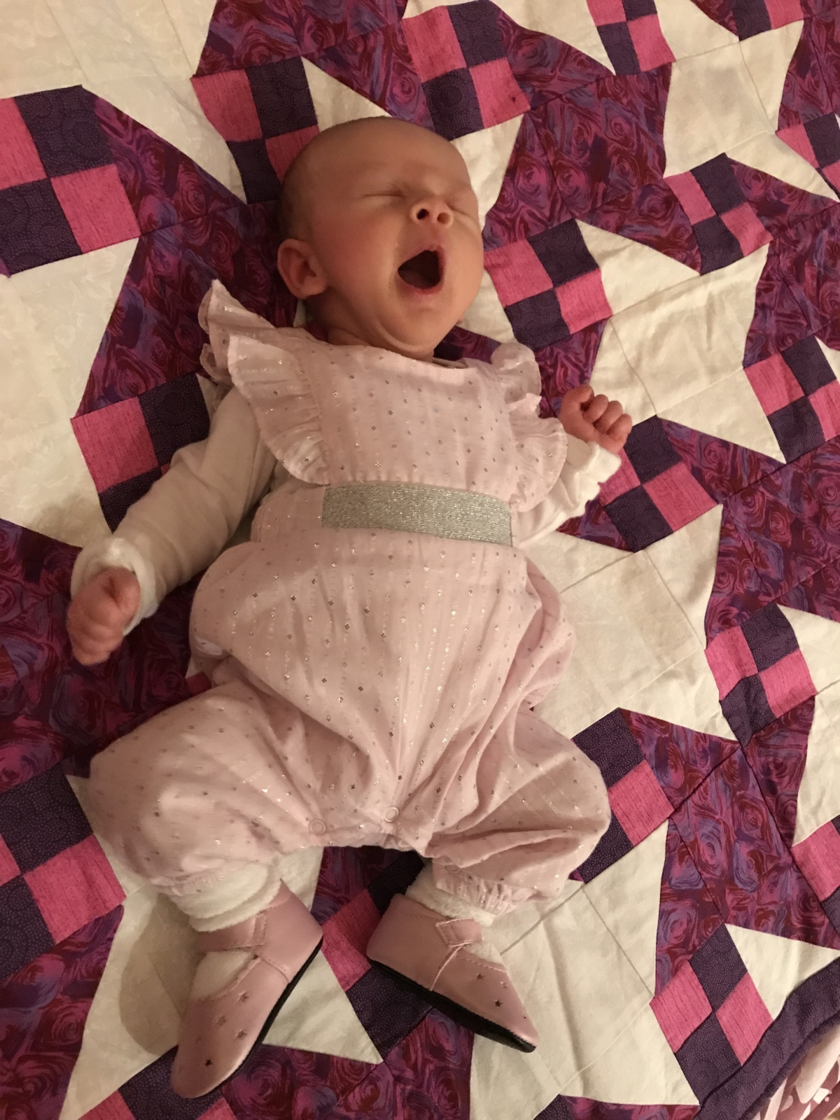 Baby yawning on a quilted blanket